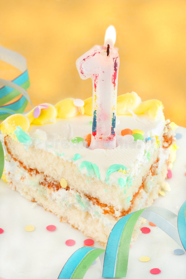 Slice of first birthday cake. With lit candle, confetti, and ribbon royalty free stock images