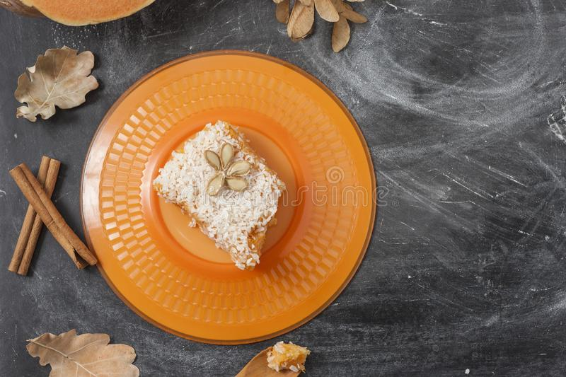 Slice of fresh homemade pumpkin pie and semolina on a orange plate on a dark background. . A Thanksgiving or holiday royalty free stock photos