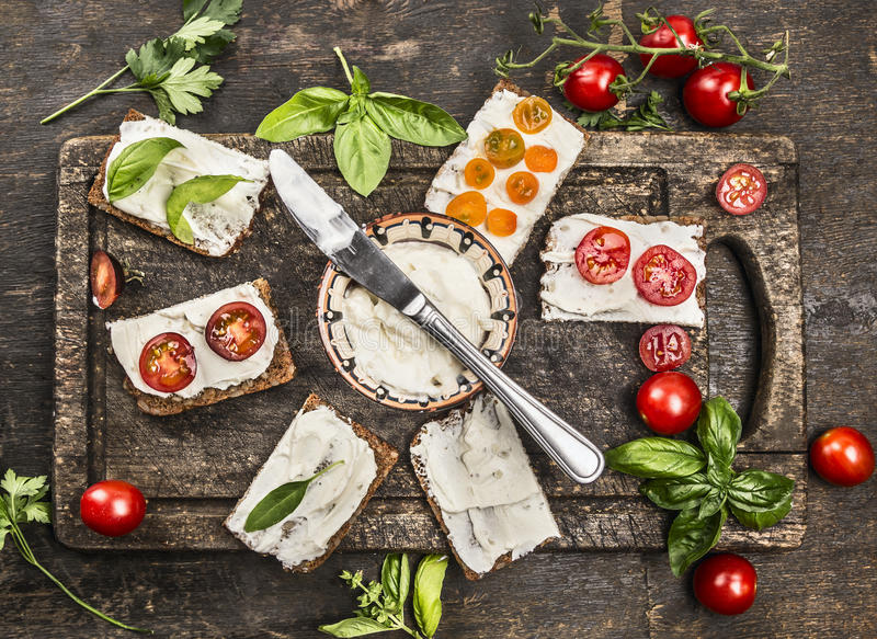 Slice of fresh rye bread with cream cheese with basil and tomatoes on vintage wooden cutting board, viewed from above royalty free stock photo
