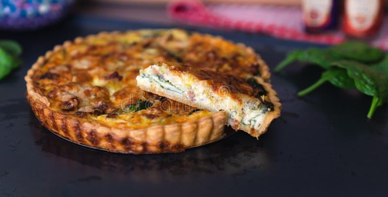 Slice frisch gebackener Bake Spinat Quiche auf dunkelblauem Hintergrund mit Kopierraum, Nahzugabe lizenzfreie stockfotos