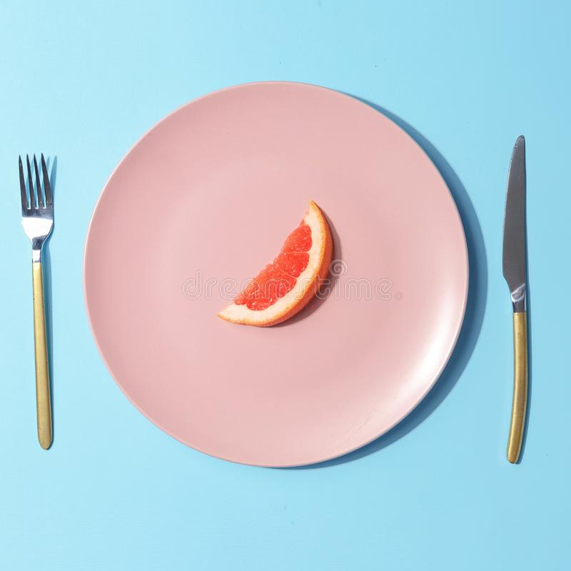 A slice of grapefruit on a pink plate. Minimalistic concept. Top view. Round background white above table clean dinner food empty dish space object isolated stock image