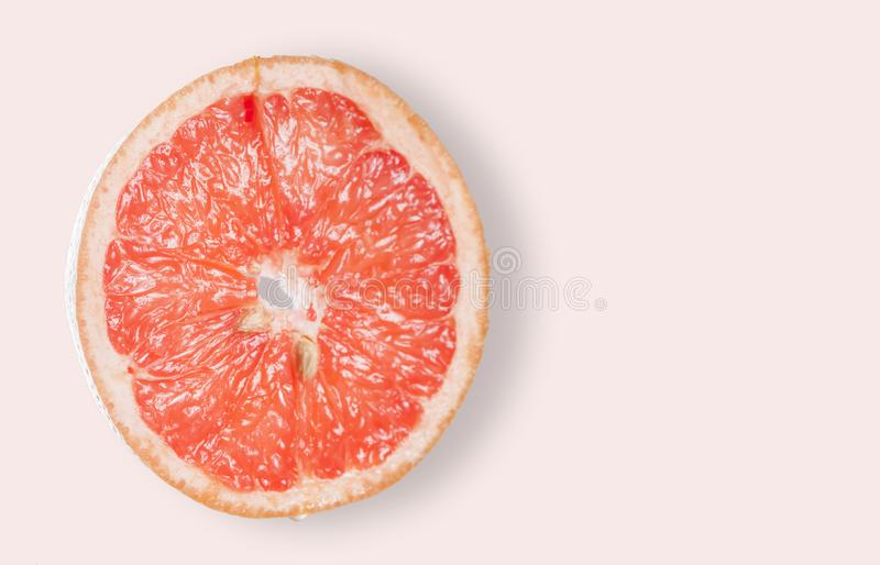 Slice of Grapefruit on Pink. A slice of Grapefruit is portrayed on a light pink background with copy-space royalty free stock images