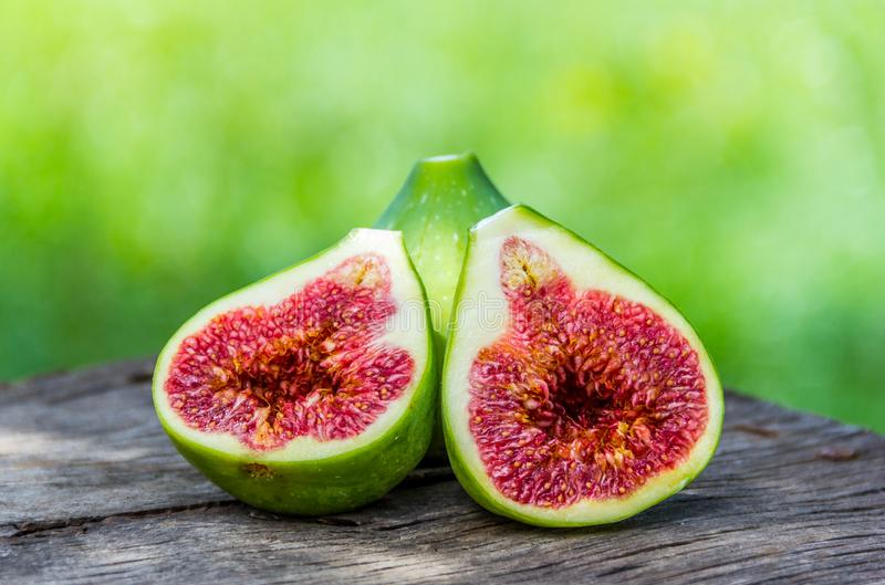 Slice of green figs. Green figs on wooden board stock photo