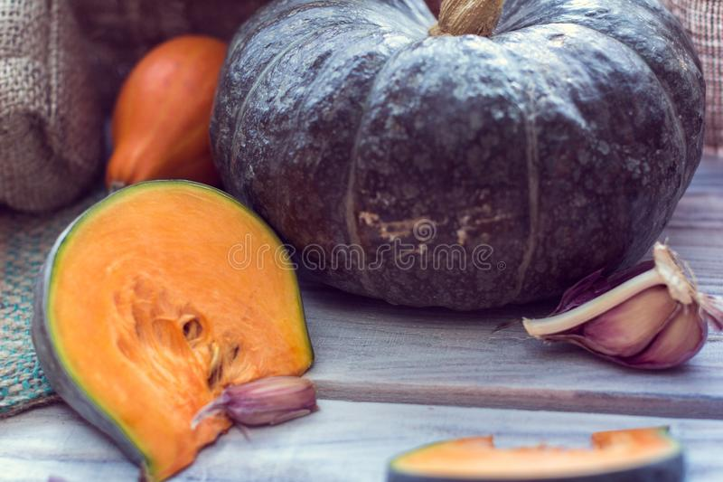 Slice of green pumpkin and other colorful pumpkins with garlic royalty free stock images