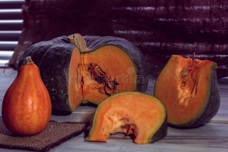 Slice of green pumpkin. On a wood background royalty free stock photo