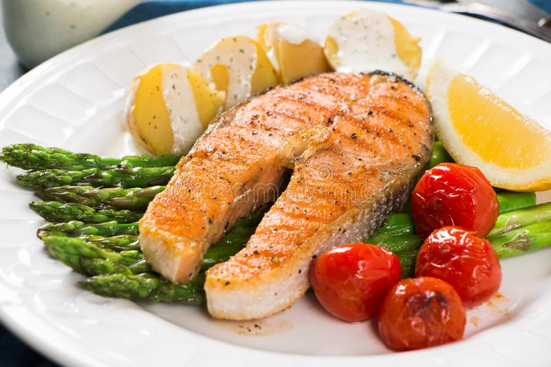 Grilled salmon with green asparagus, cherry tomato and potatoes stock photos