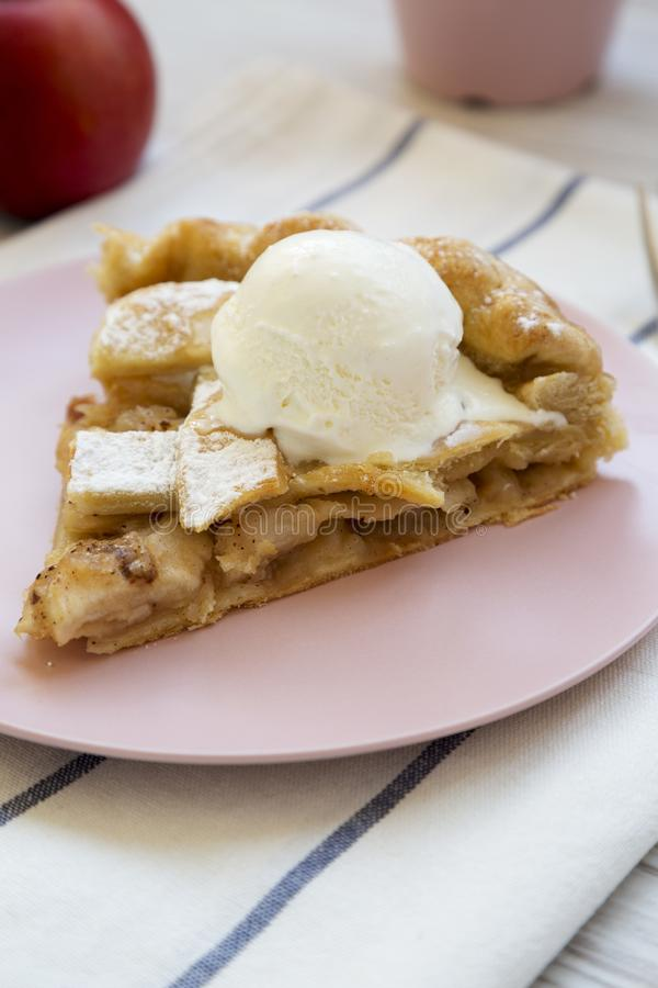 Slice of home-baked apple pie with ice cream on pink plate, side view. Close-up royalty free stock images