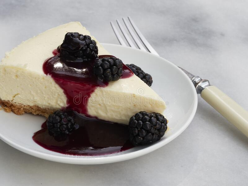 A slice of homemade cheese cake with an almond meal crust. Topped with blackberies with a blackberry sauce pour royalty free stock photography