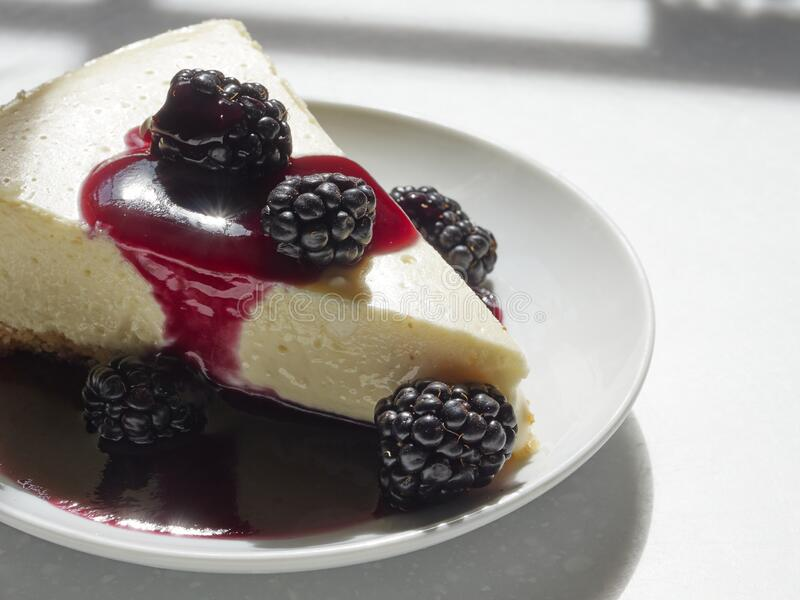 A slice of homemade cheese cake with an almond meal crust topped with blackberies. With a blackberry sauce pour royalty free stock image