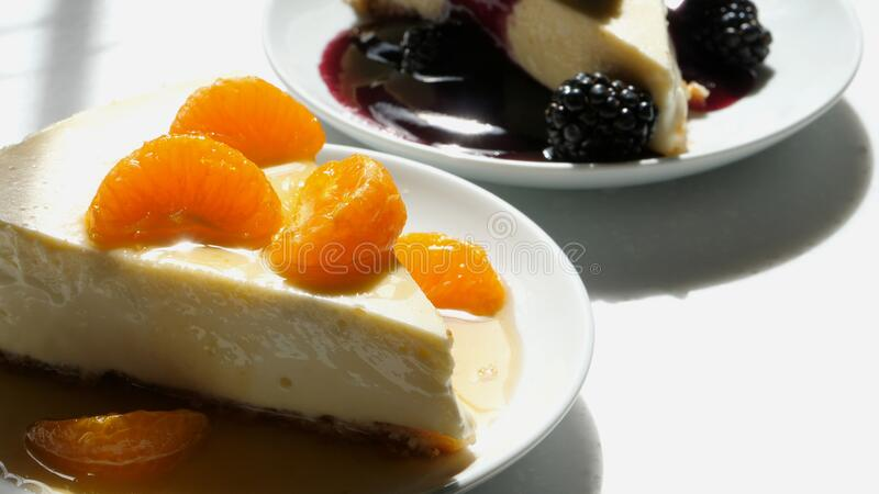 Slice of homemade cheese cake with an almond meal crust topped with mandarin oranges with an orange sauce. Pour and a blackberry topped piece royalty free stock photo