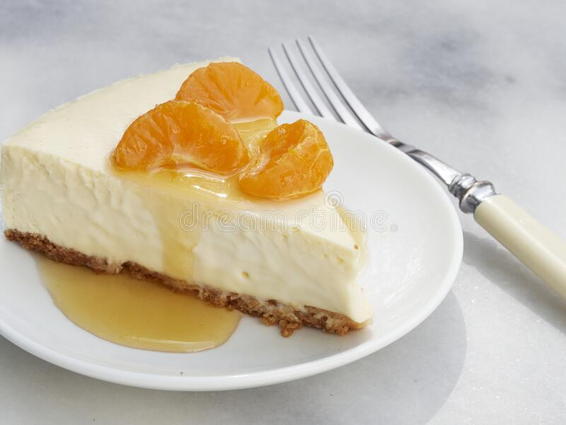 A slice of homemade cheese cake with an almond meal crust topped with mandarin oranges. With an orange sauce pour royalty free stock photos