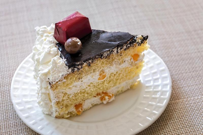 Slice of Homemade Cream Cake with Chocolate Fudge, sweets and pe royalty free stock image