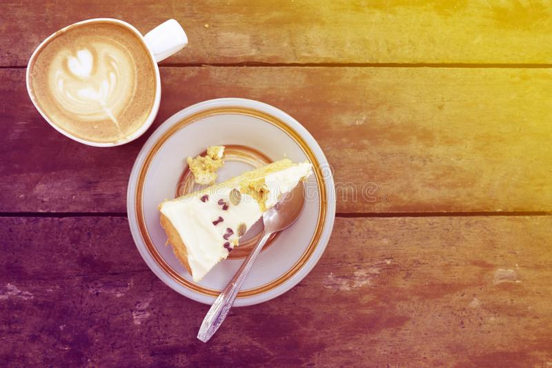 Slice of homemade pumpkin cake with cup of latte on wooden table in warm sun light stock photography