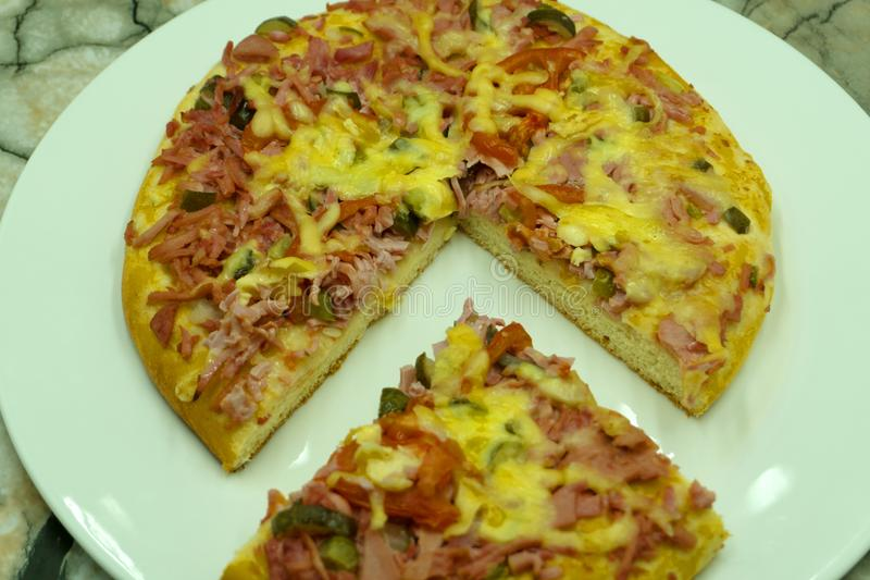 Slice of hot pizza large cheese lunch or dinner crust seafood meat topping sauce. with bell pepper vegetables delicious tasty fast stock images