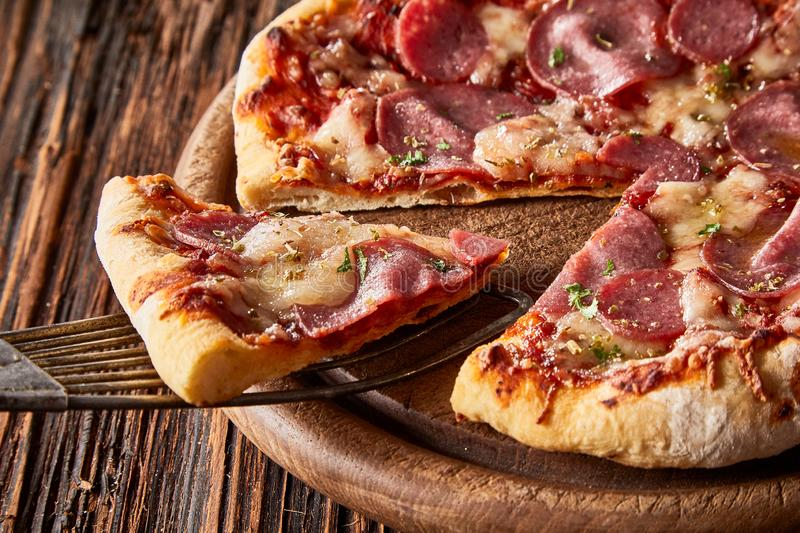 Slice of Italian pepperoni pizza on a spatula royalty free stock images