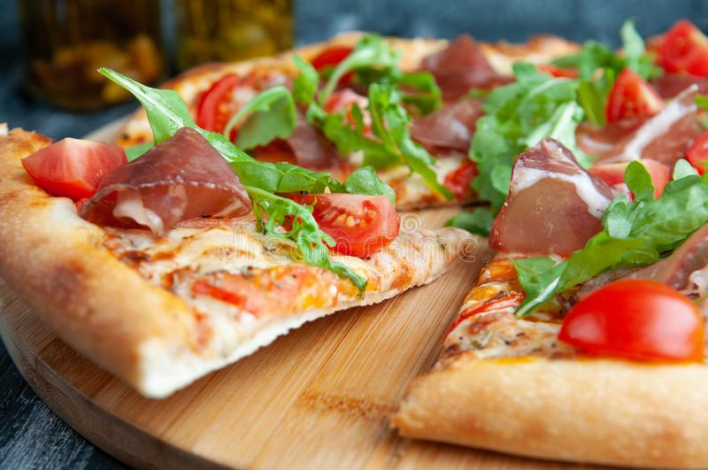 A slice of Italian pizza. With tomatoes, dried meat and arugula. Close-up. Macro. On a wooden background stock photo