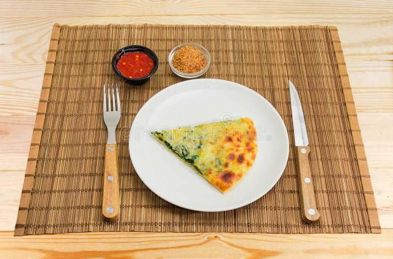 Slice of khachapuri on dish, fork and knife and seasonings stock photography
