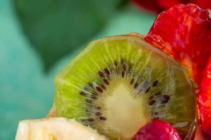 Slice kiwi and a variety of fresh fruits in sweet gelatin. Berries close-up in soft focus. Delicious dessert. stock image