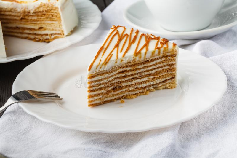 Slice of layered honey cake. Russian cake Medovik with walnuts stock photography
