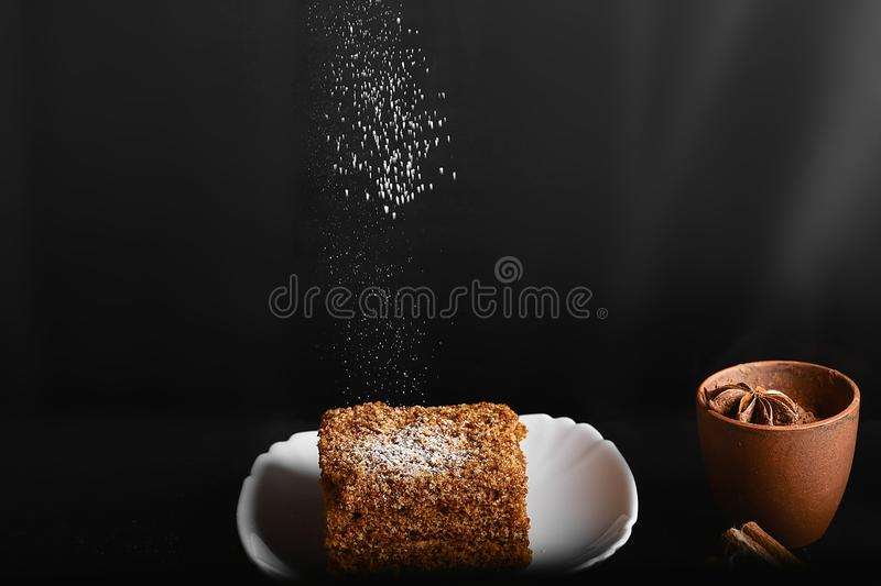 Slice of layered honey cake sprinkle with sugar powder on white plate, cocoa with anise star, on a dark background, close-up, set.  royalty free stock photography