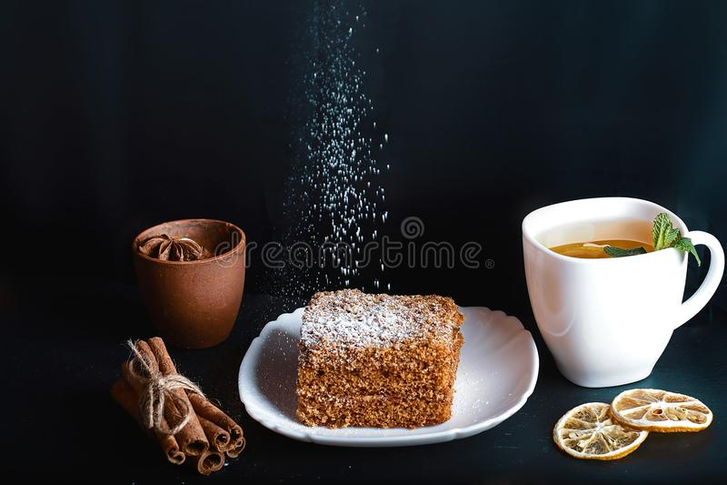 Slice of layered honey cake sprinkle with sugar powder on white plate, cocoa with anise star, mint, dried lemons, sticks of cinnam. On, on a dark background royalty free stock images
