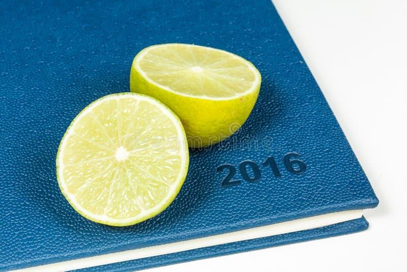 Slice of lemon on blue diary. Of year 2016 royalty free stock photos