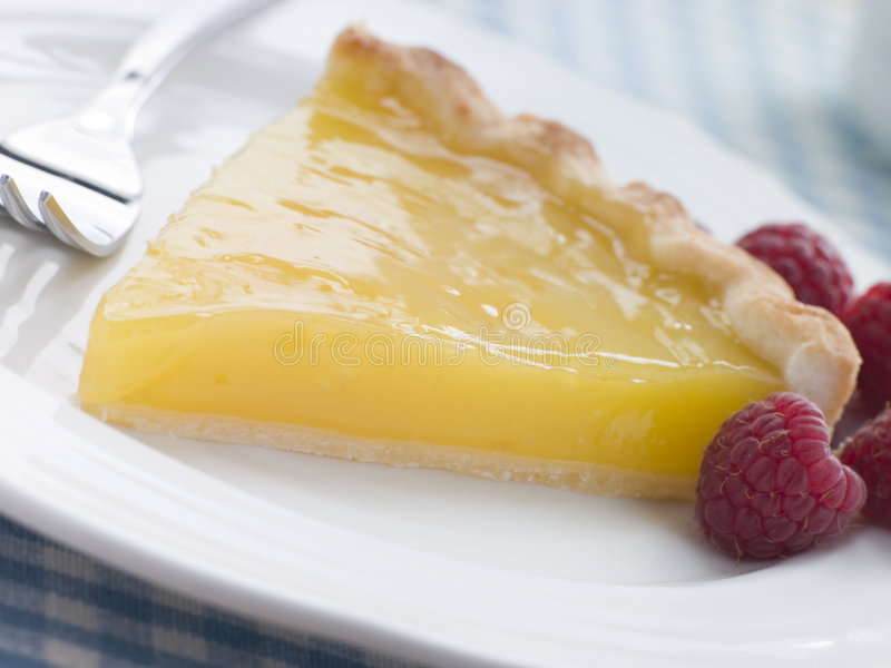 Slice of Lemon Curd Tart with English Raspberries. And a fork on a plain white plate royalty free stock photography
