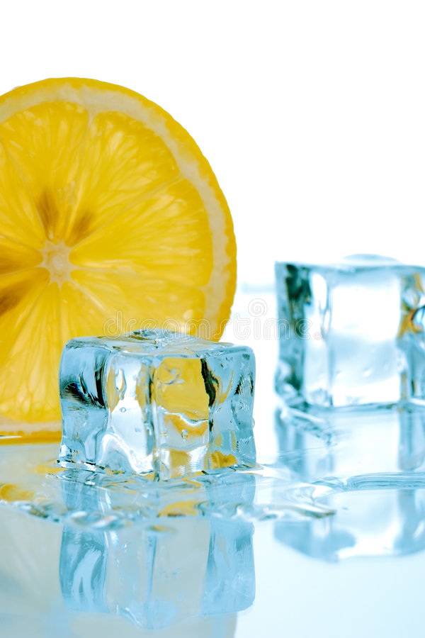 Slice of lemon and ice cubes. Two ice cubes melted in water and slice of lemon on reflection surface ready to be added to a cocktail stock photo