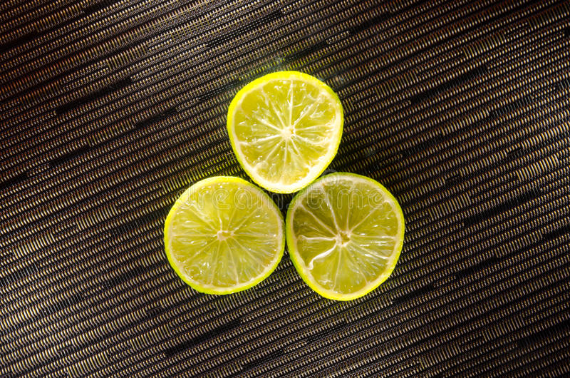 Slice of lemon or lime on black background with stripes royalty free stock images