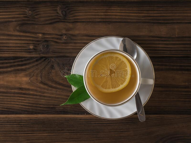 A slice of lemon in a white Cup of tea and a metal spoon on a wooden table. Flat lay. stock photos