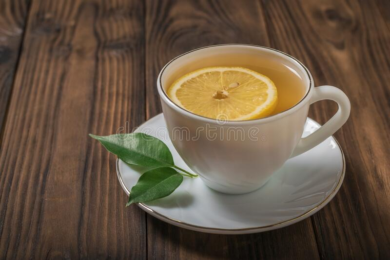 A slice of lemon in a white Cup of tea on a wooden table. stock photography