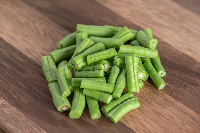 Slice of long bean on wood cutting board. royalty free stock images