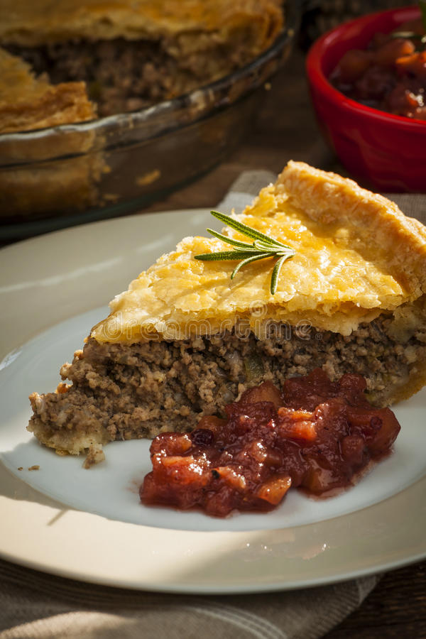 Slice of meat pie Tourtiere. Slice of traditional pork meat pie Tourtiere with apple and cranberry chutney from Quebec, Canada stock photos