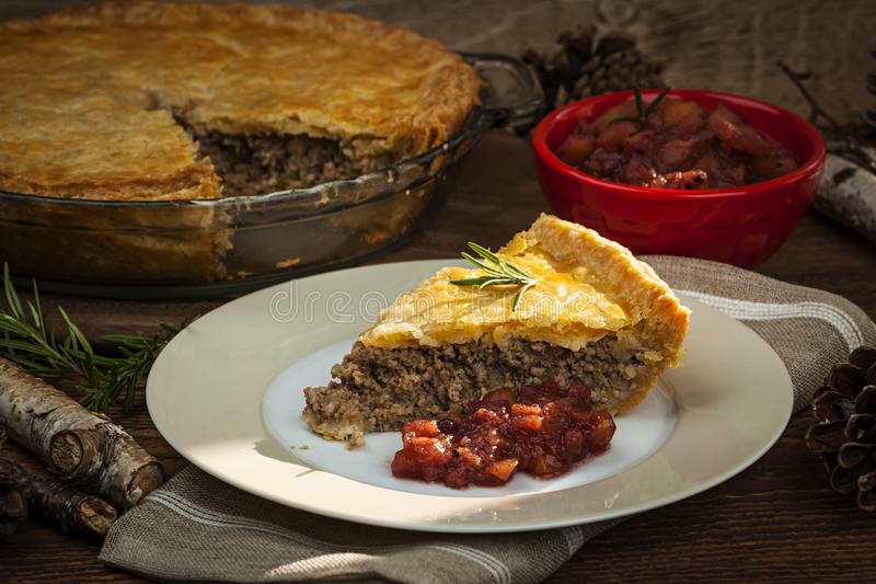 Slice of meat pie Tourtiere. Slice of traditional pork meat pie Tourtiere with apple and cranberry chutney from Quebec, Canada royalty free stock photography