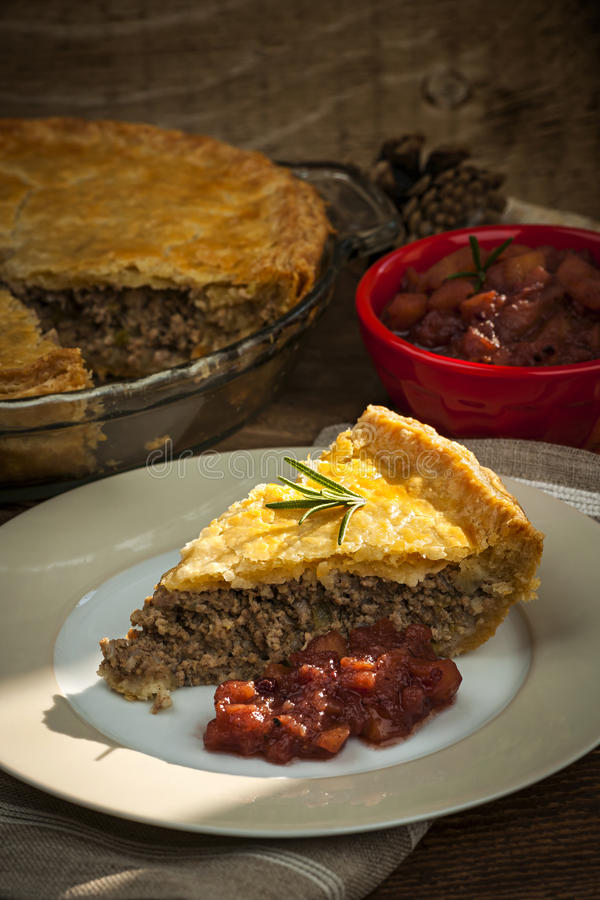 Slice of meat pie Tourtiere. Slice of traditional pork meat pie Tourtiere with apple and cranberry chutney from Quebec, Canada stock images