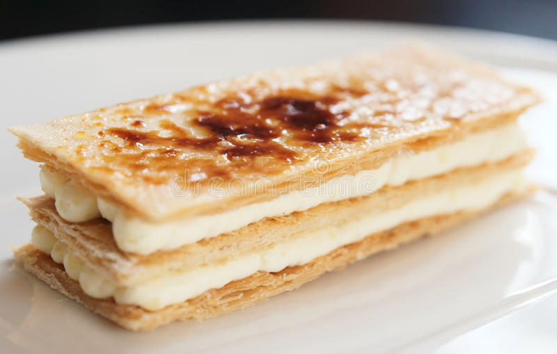 Slice of mille-feuille cake. On porcelain plate stock images