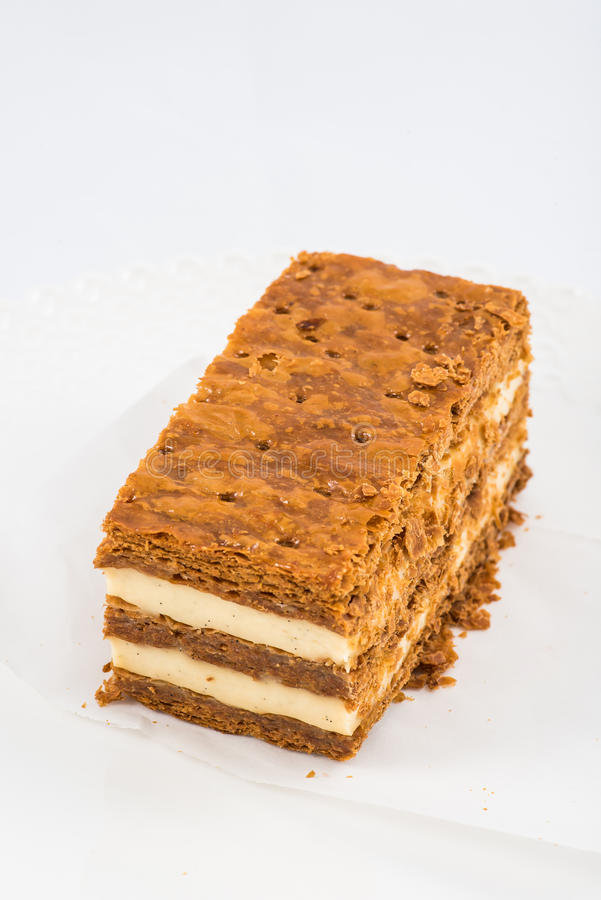 A slice of mille-feuille. Top view of a slice of mille-feuille with vanilla cream and crusty layers on white background royalty free stock photography