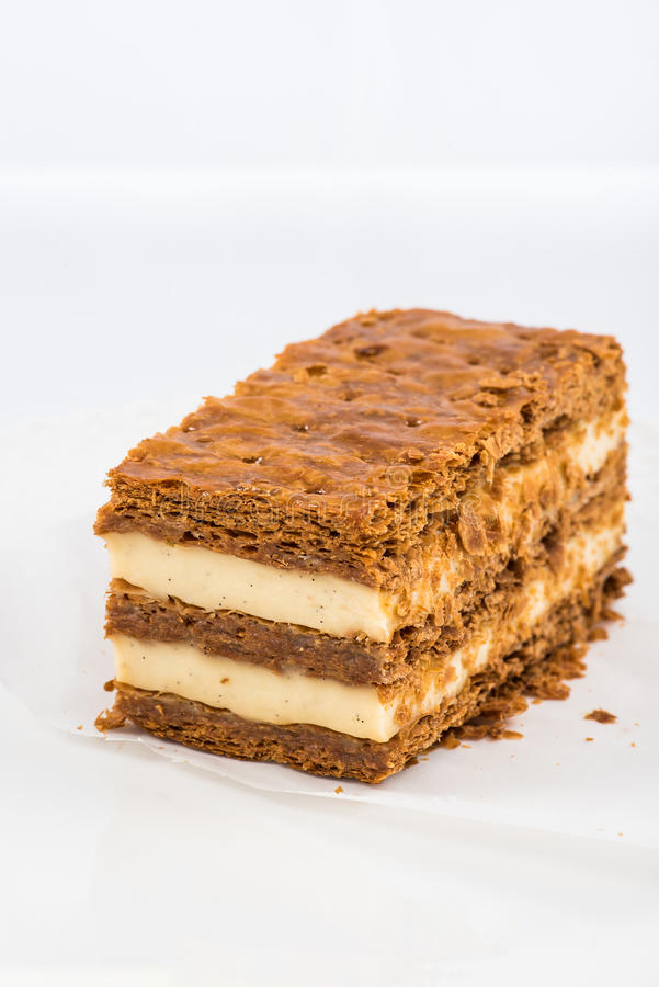A slice of mille-feuille. Top view of a slice of mille-feuille with vanilla cream and crusty layers on white background royalty free stock photos