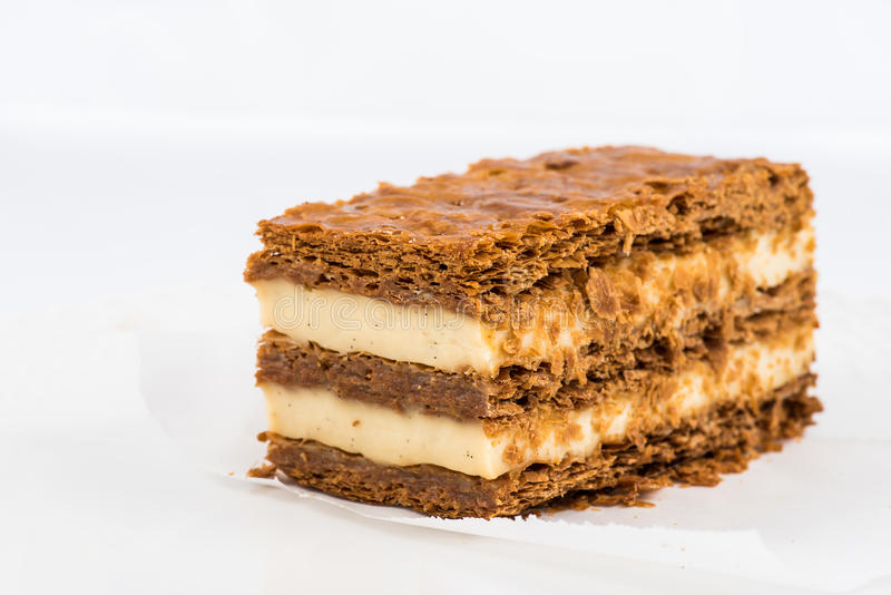 A slice of mille-feuille. With vanilla cream and crusty layers on white background royalty free stock image