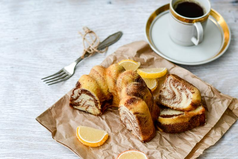 Bundt marble cake, cup of coffee and lemon slices royalty free stock photo