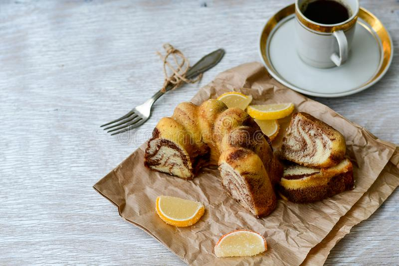 Bundt marble cake, cup of coffee and lemon slices stock image