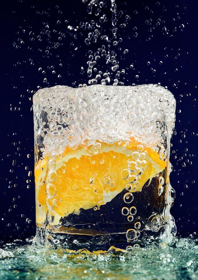 Slice of orange falling down in water. Slice of orange falling down in glass with water on deep blue stock image