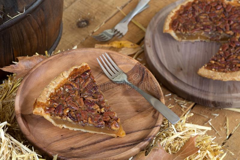 Slice of Pecan Pie. On a wooden plate royalty free stock photo