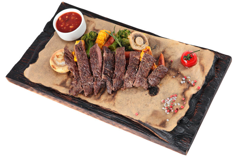 Slice into pieces fried Skirt steak with vegetables on white. royalty free stock images