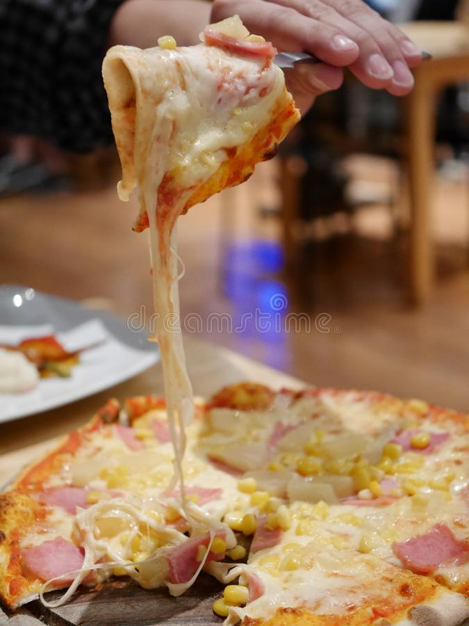 A slice of pizza lifted up royalty free stock photography