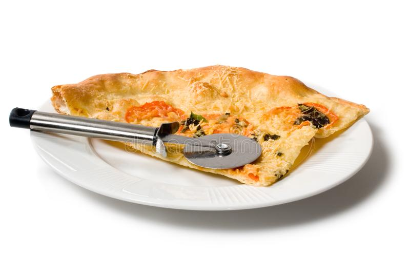Slice of pizza on white plate with pizza cutter royalty free stock photography