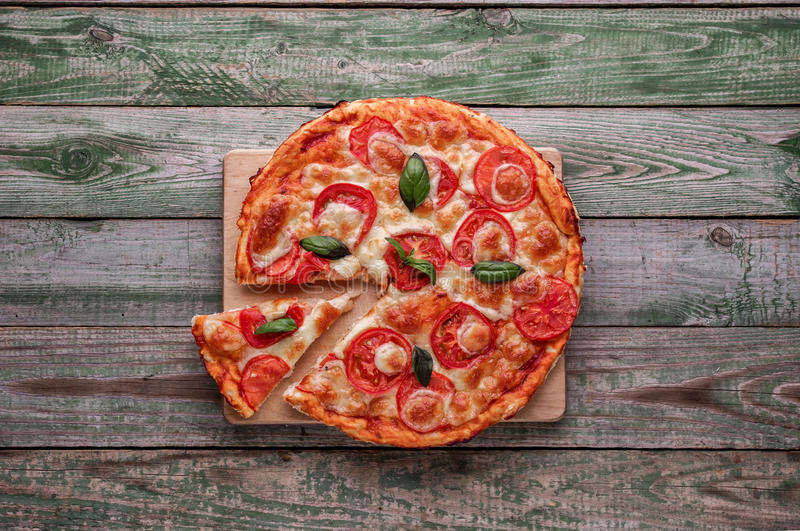 Slice of pizza on wood chopping board. Top view. Green rustic wood table royalty free stock image