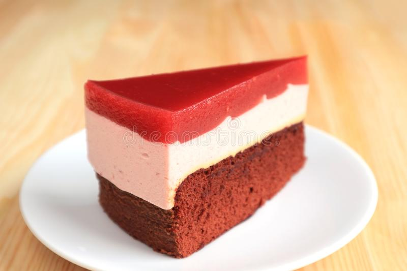 Slice of Raspberry Mousse with Chocolate Layer Cake Served on Wooden Table royalty free stock image