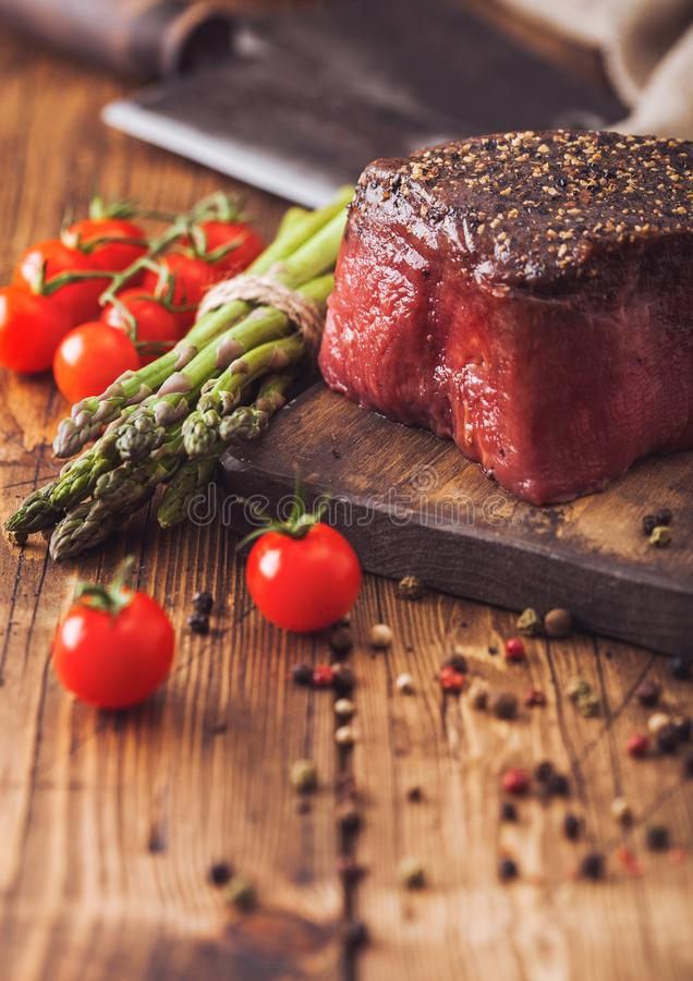 Slice of Raw Beef Topside Joint with Salt and Pepper on wooden chopping board with tomatoes garlic and asparagus tips royalty free stock image