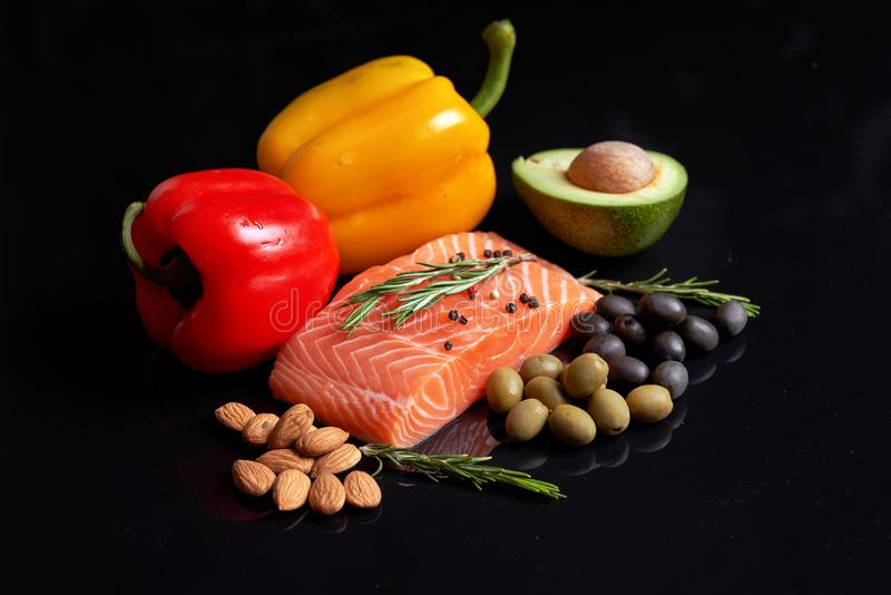 A slice of raw salmon fillet with a sprig of rosemary, red and yellow sweet peppers, almond nuts, green and black olives and slice. D avocado fruit. Healthy food royalty free stock image
